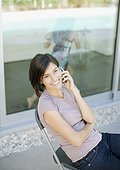 Woman talking on cell phone on patio