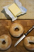Bagels and butter on wooden chopping board.