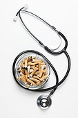 Cigarettes in ash tray with stethoscope.