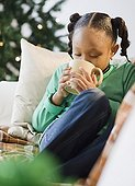 African American girl drinking hot chocolate on sofa
