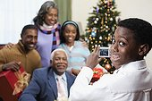 African boy taking Christmas portrait of family