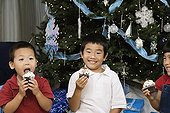 Korean siblings holding cupcakes next to Christmas tree