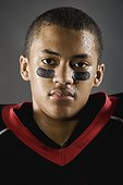 Mixed race football player with face paint under eyes