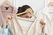 Mixed race woman holding shirt on hanger