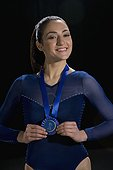 Mixed race gymnast with blue ribbon