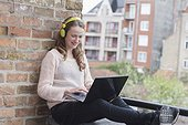 Mid-adult woman with headphones on sitting on balcony railing and using laptop. (Belgium, Brugge)