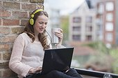 Mid-adult woman with headphones on sitting on balcony railing holding coffee cup and using laptop. (Belgium, Brugge)