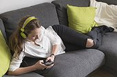 Mid-adult woman lying on sofa and listening to music from smart phone