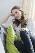 Mid-adult woman sitting on sofa with legs curled up and smiling