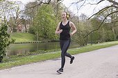Mid-adult woman with headphones on jogging by canal in park. (Belgium, Brugge)