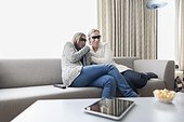 Women in 3d glasses sitting on sofa in living room