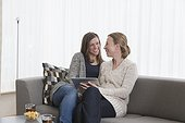 Smiling women sitting on sofa in living room and holding tablet