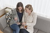 Women sitting on sofa in living room and looking at tablet