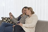 Women sitting on sofa and looking at phone