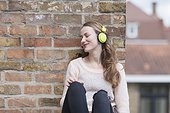 Mid-adult woman with eyes closed and headphones on sitting by brick wall