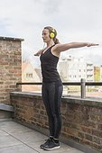Mid-adult woman exercising on balcony with headphones on