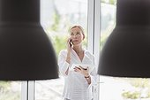 Woman talking on phone and using digital tablet