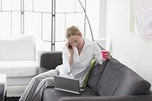 Woman talking on phone and using laptop in living room