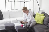 Woman using laptop in living room