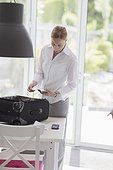 Woman packing suitcase for business travel