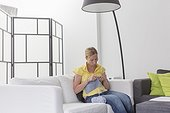 Mature woman knitting in modern living room