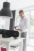 Mature woman packing suitcase and passport
