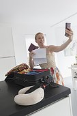 Happy mature woman packing suitcase for vacations and taking selfie