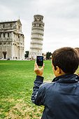 Italy, Tuscany, Pisa, Rear view of teenage boy (16-17) photographing Leaning Tower of Pisa with smartphone