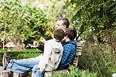 Father and two sons (10-11) sitting on bench in park and looking at smartphone