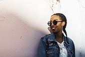 Smiling young woman wearing sunglasses and denim jacket standing by white wall