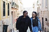 Portugal, Lisbon, Two smiling young women walking outdoors