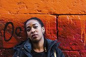 Serious young woman leaning against orange wall