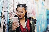 Portugal, Lisbon, Smiling young woman looking at smartphone, leaning against wall