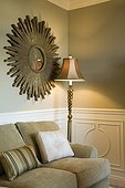 Floor Lamp and Starburst Mirror in Corner of Living Room