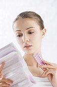 young woman reading pills leaflet