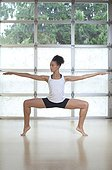Young woman doing ballet-style stretch on toes in fitness studio