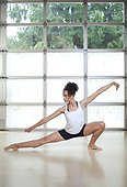 Young woman doing ballet-style lunge stretch in fitness studio