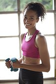 Young woman smiling and holding barbells