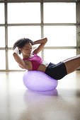 Young woman exercising on fitness ball