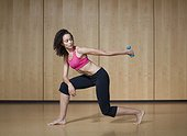 Young women exercising with small barbell in dance studio