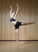 Young woman doing ballet warm-up in dance studio