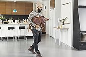 Full length of male architect with bag using mobile phone while walking in kitchen