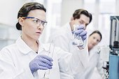 Female scientists examining chemical at laboratory