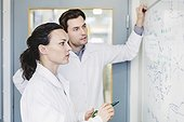Scientists discussing plan on whiteboard in laboratory