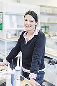 Portrait of smiling female scientist standing in laboratory