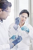Male and female scientists examining sample in laboratory