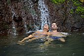 Couple enjoying bath under waterfalls