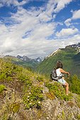 Female hiker on Bird Ridge viewing scenery, Southcentral Alaska, Summer