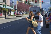 Young adult couple looking at smart phones as they cross a downtown street, Anchorage, Southcentral Alaska, Summer