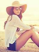 Fashion portrait of beautiful young woman on the beach at sunset, bright warm sunny color tones